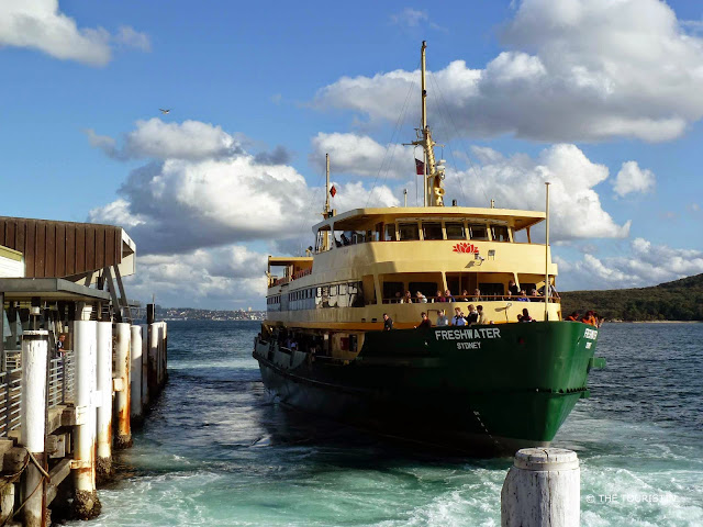 A large yellow-green-coloured passenger ferry with the name Freshwater Sydney arriving at the pier under a bright blue sky with white fluffy clouds.