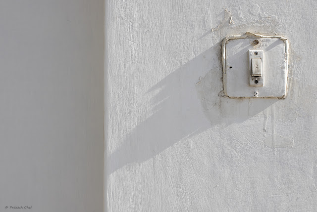 A Minimalist Photograph of an Old House Door Bell with Long Shadow on Textured White Wall