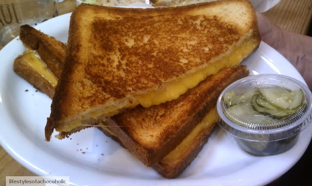 two large pieces of grilled cheese on a white plate next to a cup of pickles