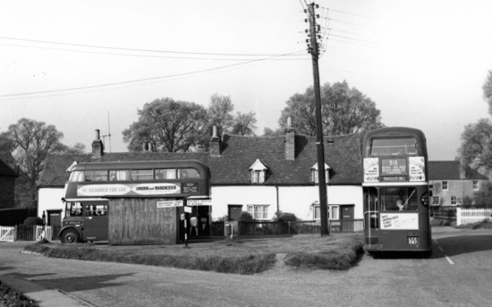 Photograph of Early morning buses at Nash's Corner. 303A to New Barnet Station and school bus on the right going to Mardley Hill. May 1966