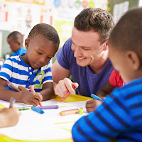 image of a white male teacher smiling, coloring with a couple of black toddlers.