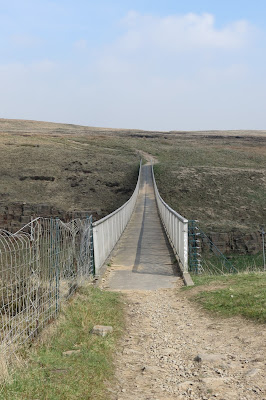 A narrow footbridge stretched out ahead, connecting the moors.