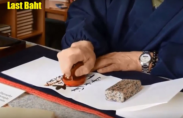 a calligrapher applies the official red temple stamp inside the seal book