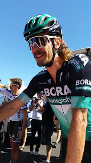 "Portrait of a smiling Daniel Oss. He is wearing the black and greed Bora-Hansgrohe colours with large white letters""BORA"" dominating the design. He is wearing reflective sunglasses with white trim.  His shoulder length wavy hair is seen at the back of his neck."