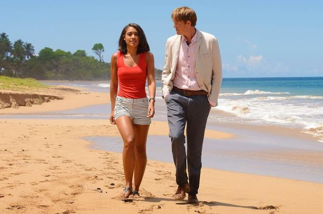 Two character from Death in Paradise walking along a Caribbean beach