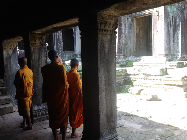 four saffron-robed monks walk the ancient ruins of Angkor Wat in Siem Reap, Cambodia