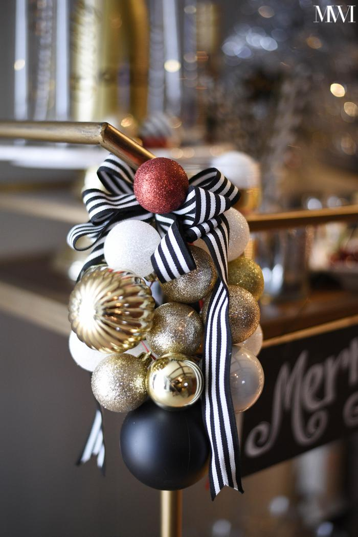 Black, white, red and gold cluster of ornaments on a bar cart