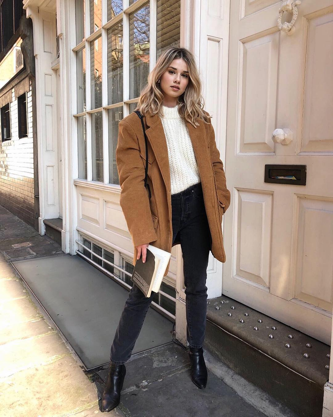 A Stylish Everyday Winter Outfit Idea to Try Now — Iga Wysocka in a camel jacket, white sweater, black jeans, and boots