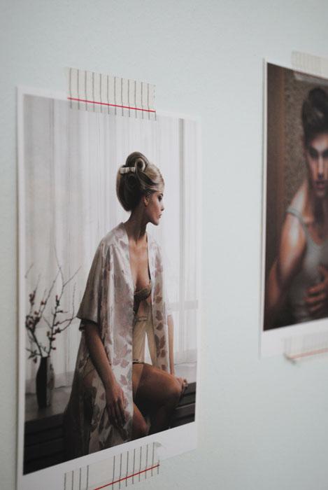 Kunstkaart met een foto van Erwin Olaf van een vrouw in een satijnen badjas die op een vensterbank zit.