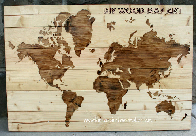 A wooden world map art with the world partially stained showing the progress