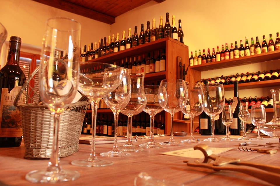 Immagine di una degustazione di vini con bottiglie e bicchieri