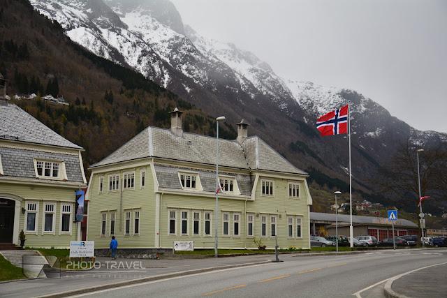 Flaga Norwegii powiewająca nad fiordami