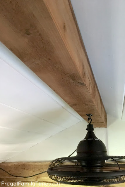 finished shiplap ceiling with wood faux beam