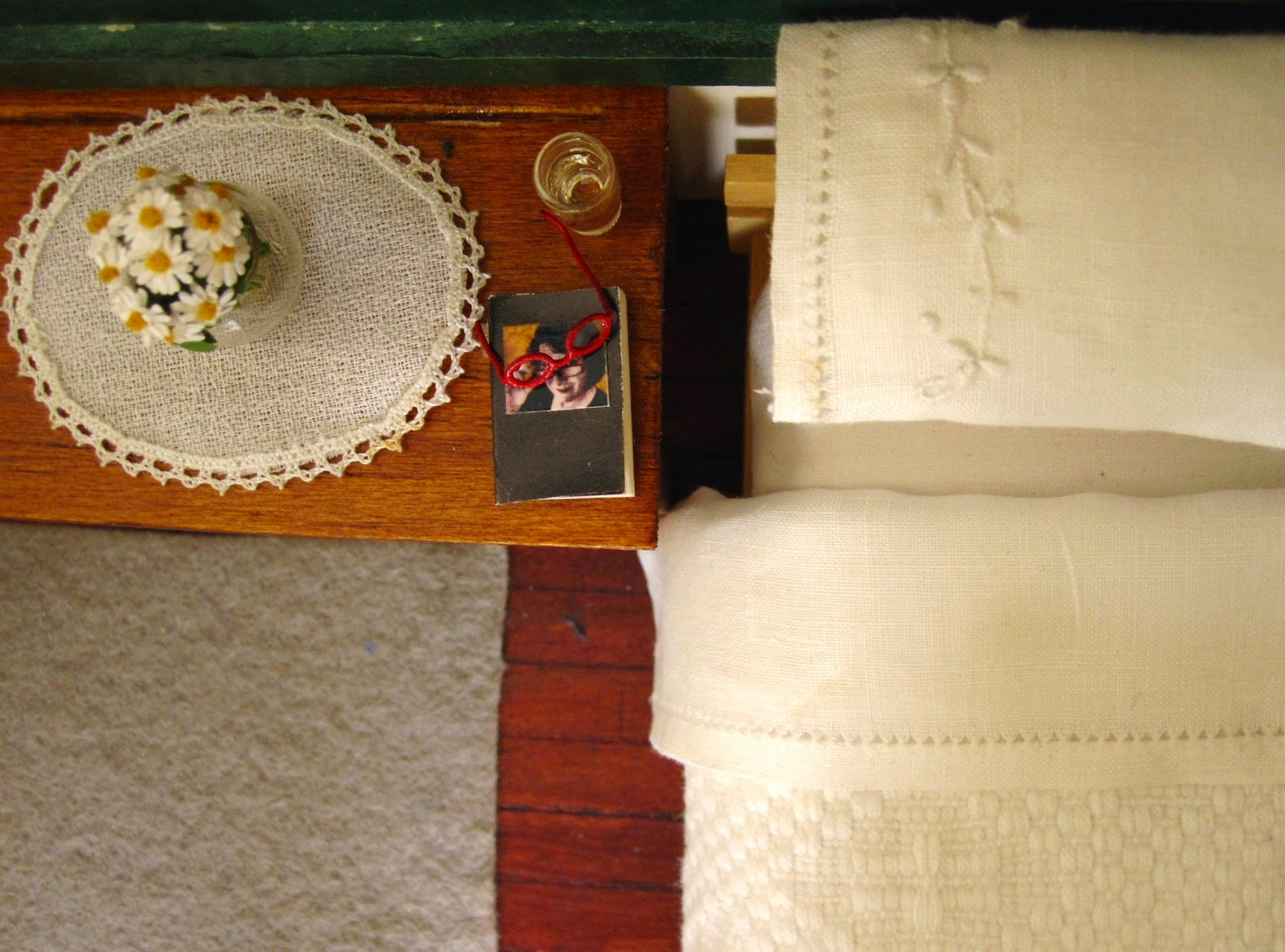 View from above of a modern miniature doll's house bed with white cotton embroidered bedding . On the bedside table is a glass of water, a diary and reading glasses and a vase of daisies.