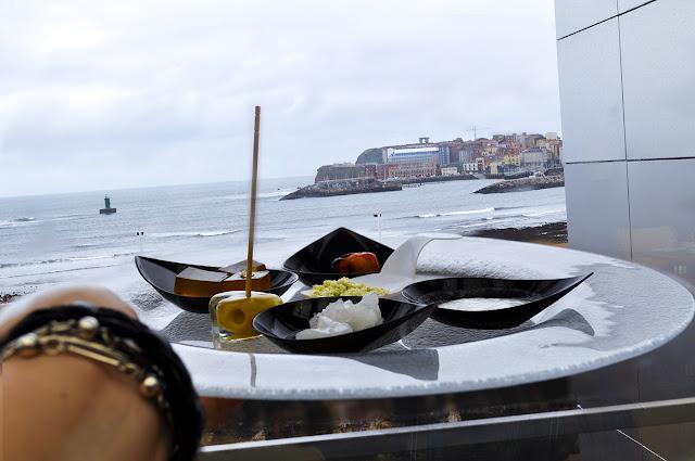 las vistas de la playa de poniente y en primer plano un plato con las distintas degustaciones
