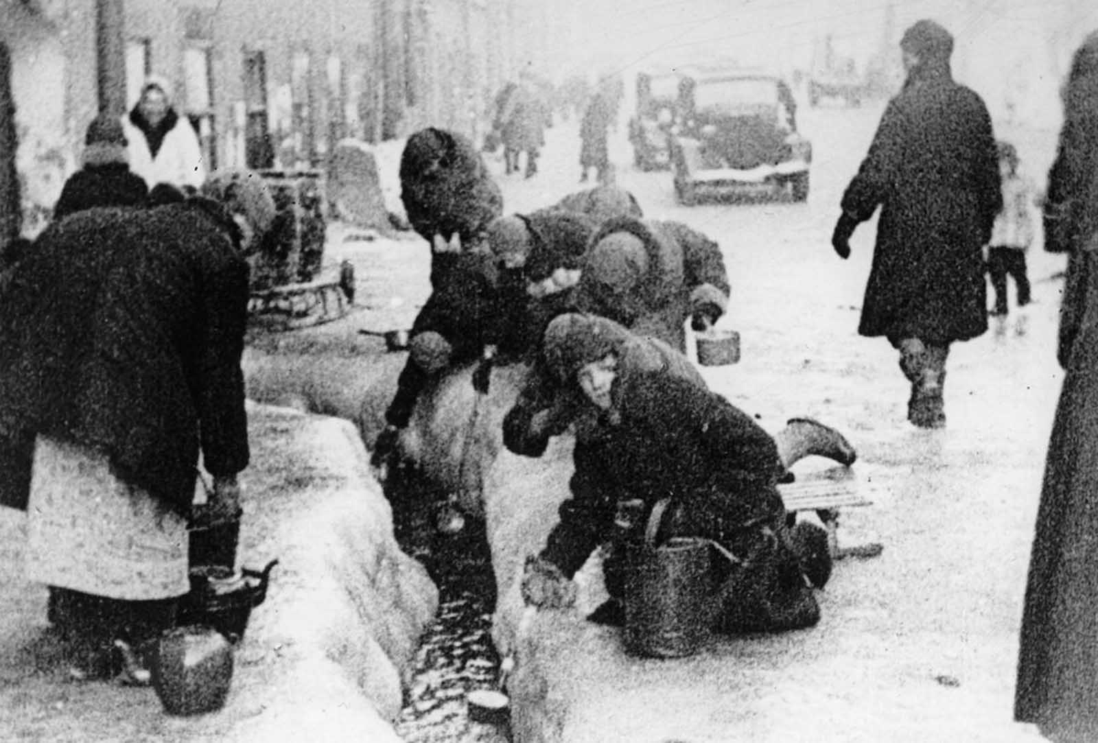 This photo, taken in the winter months of 1942, shows citizens of Leningrad as they dip for water from a broken main, during the nearly 900-day siege of the Russian city by German invaders. Unable to capture the Leningrad (today known as Saint Petersburg), the Germans cut it off from the world, disrupting utilities and shelling the city heavily for more than two years.