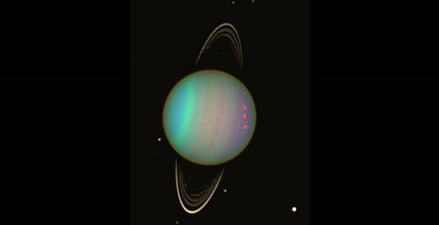 Uranus is seen in this false-color view from NASA's Hubble Space Telescope from August 2003. The brightness of the planet's faint rings and dark moons has been enhanced for visibility. Credits: NASA/Erich Karkoschka (Univ. Arizona)