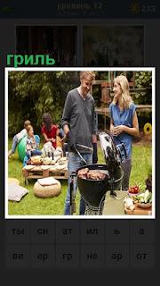 мужчина жарит мясо на гриле, рядом стоит женщина, сзади компания людей