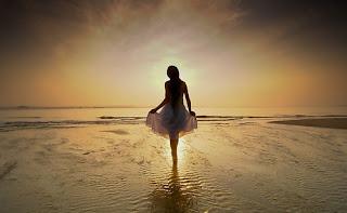Όρθια γυναίκα σε παραλία την αυγή.