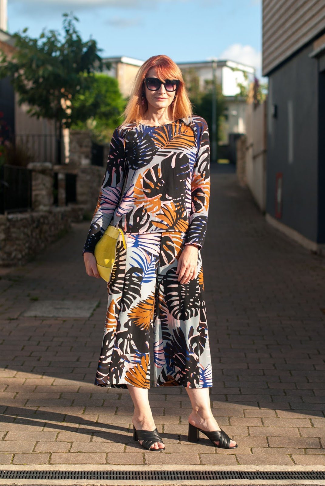 Palm print co-ords: Long sleeve top and wide leg crop trousers culottes pants  yellow suede clutch bag  black crossover block heel mule sandals  statement oversized earrings  cat eye sunglasses | Not Dressed As Lamb, over 40 style