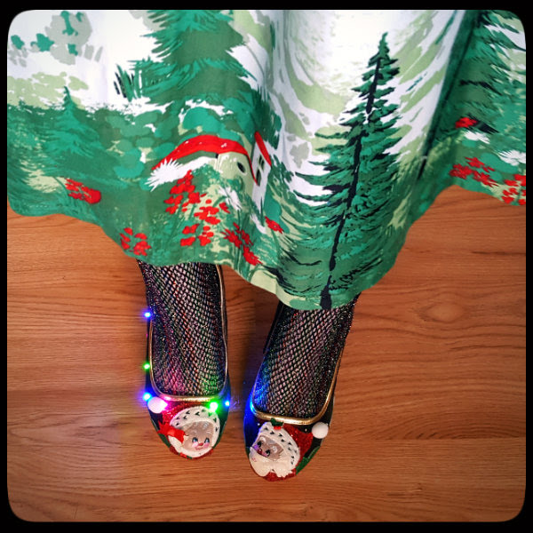 view from above of Lindy Bop Alpine print dress, fishnet tights and Irregular Choice light up Christmas shoes