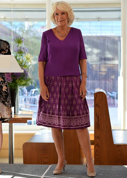 Camilla, the Duchess of Cornwall attended a literacy event for The Royal Society of Literature at the British Library. purple top and print skirt