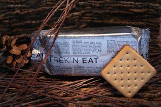 Die silberne Packung Trek'n Eat Kekse umgeben von Ästen. Vor der Packung lehnt ein Keks