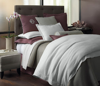 Luxury bed done up in plum and gray with white sheeting