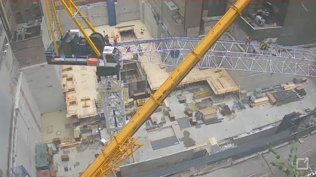 Photo of crane arm being connected to the crane
