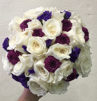 White rose bridal bouquet with pops of plum and purple by Stein Your Florist Co.