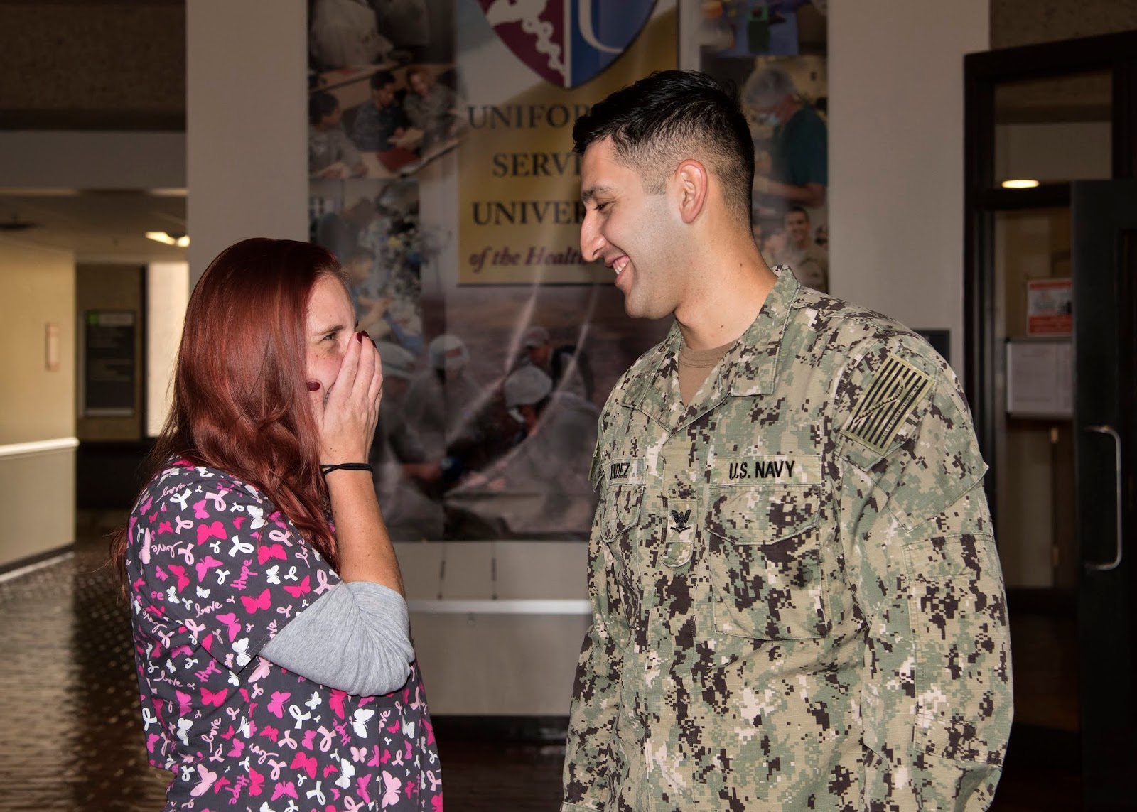 A female on the left, wearing medical scrubs covers her face while laughing at a man in a U.S. Navy uniform. They are standing in front of the entrance to the university's medical clinic.