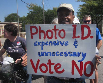 Man holding hand-painted sign reading Voter ID is expensive unnecessary VOTE  NO