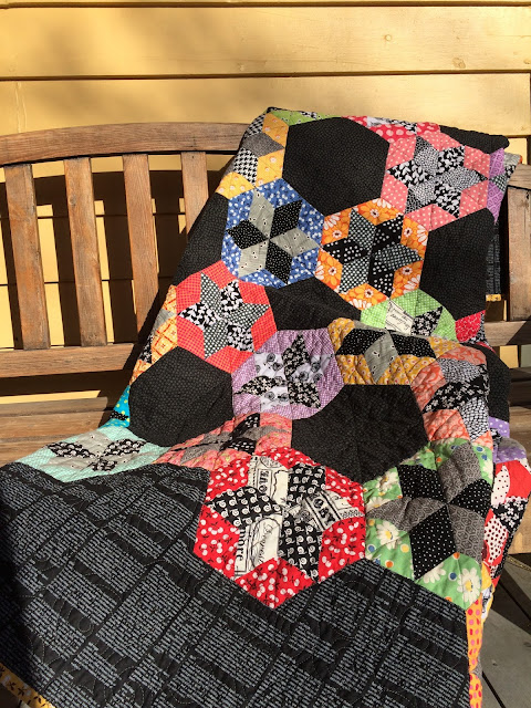 scrap quilt diamond English paper pieced blocks appliquéd onto a black background