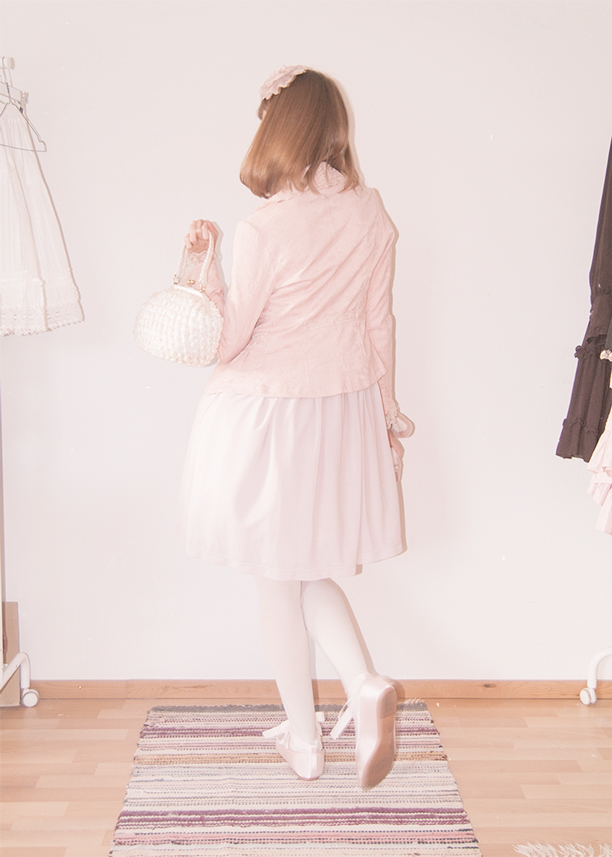 a girl dressed in a pink innocent world lolita dress walking away from camera
