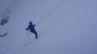 Winter mountaineering abseiling off a snow bollard