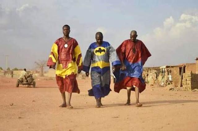 tres hobres aficanos con túnicas de superhéroes, uno de ellos de batman
