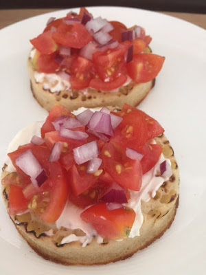 2 crumpets topped with cream cheese, tomato and red onion