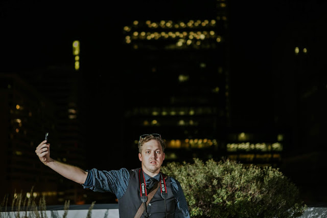 A Man Stands on Top of a Building at Night holding his phone out to provide a light source on his face