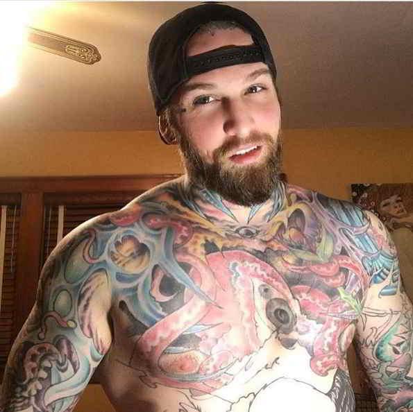 Imagen de un hombre con tatuajes biomecánico en el pectoral y brazo