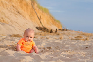 Position and support baby at the beach using sand