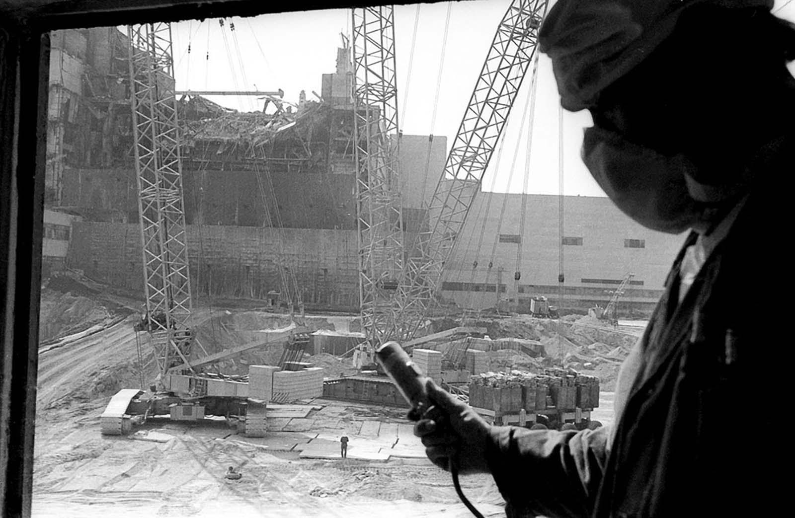 Un trabajador de la planta de energía nuclear de Chernobyl sostiene un dosímetro para medir los niveles de radiación, con el sarcófago en construcción, destinado a contener el reactor destruido, visible en el fondo, en esta foto tomada en 1986.