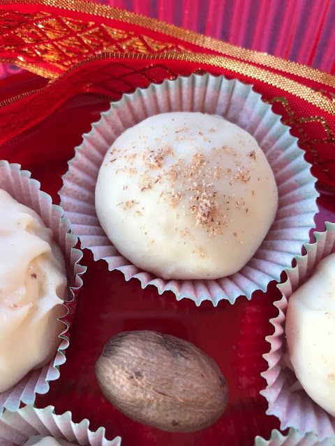 Close-up of an eggnog truffle with freshly grated nutmeg on top.