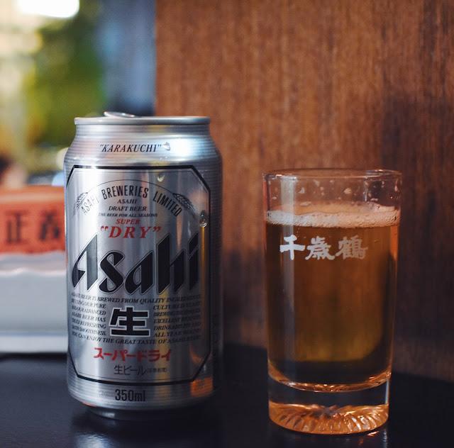 『咔』的一聲,我打開瓶裝的Asahi啤酒,喝了一口,忍不住皺了一下眉頭,要是啤酒能再冰一點應該會更好。