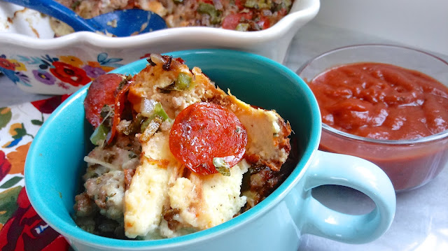 a serving of Pizza Crust Bread Pudding in a blue bowl next to a dish of pizza sauce with the casserole in the background