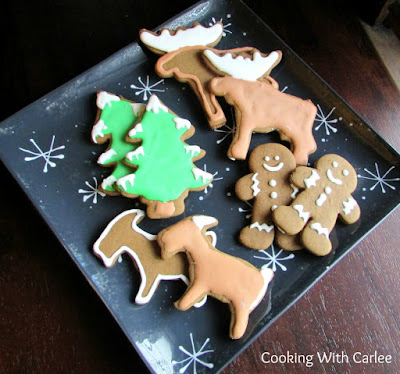 plate of german gingerbread cookies cut into men, moose, trees and goats frosted with royal icing