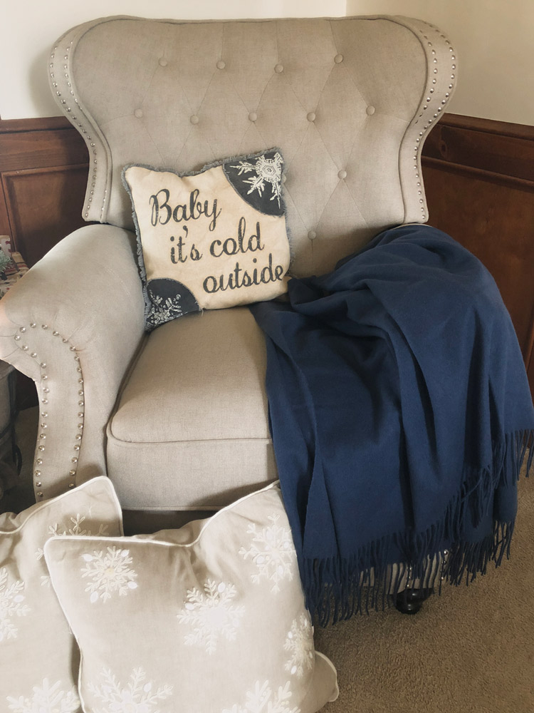 tufted chair with baby it's cold pillow and throw