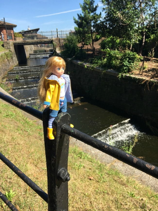 Lottie-Doll-Muddy-Puddles-sitting-on-railings-in-park