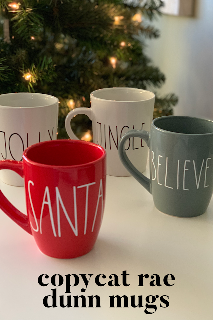 Four mugs, two white, one red and one gray that say Jingle, Believe, Jolly and Santa sitting on a white table by a lit Christmas tree.