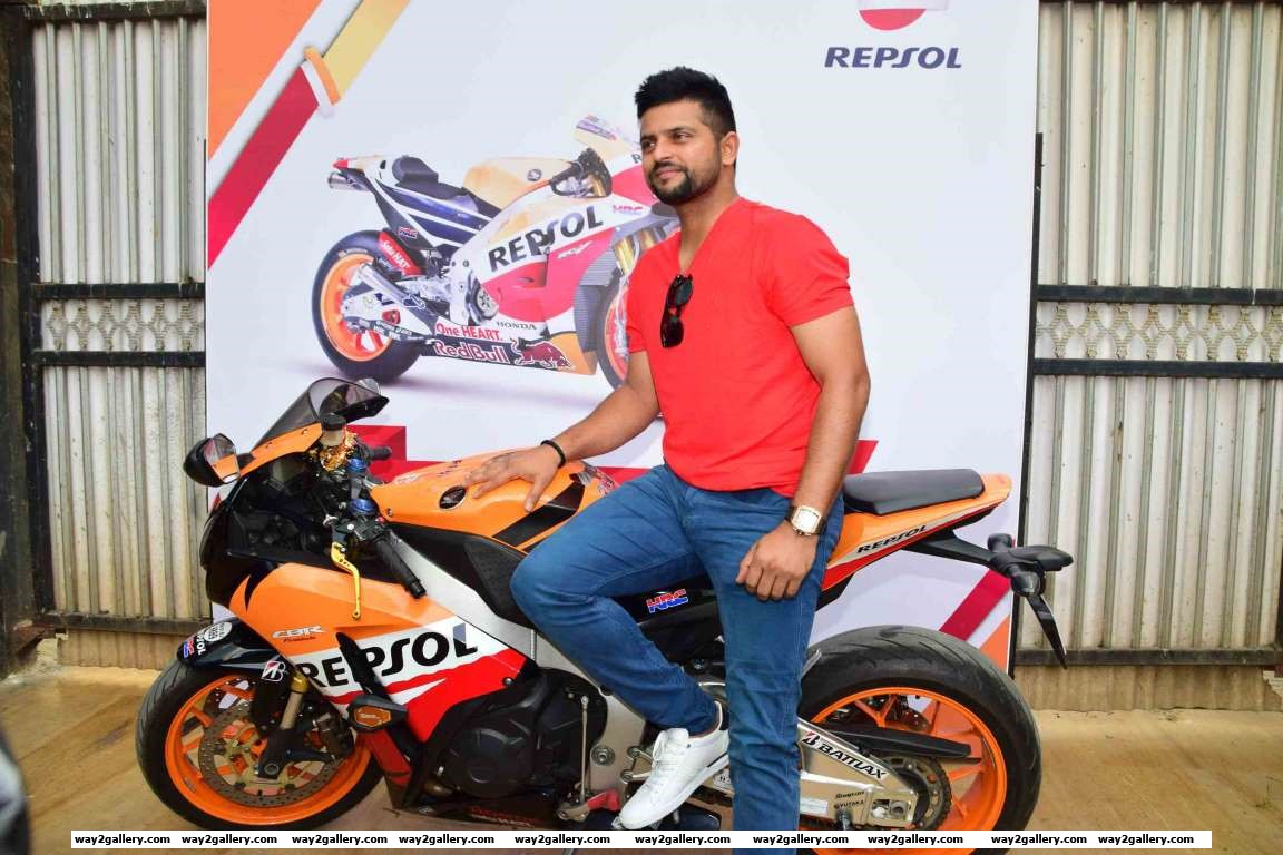 Suresh Raina poses for photographers during the launch of Repsol lubricants