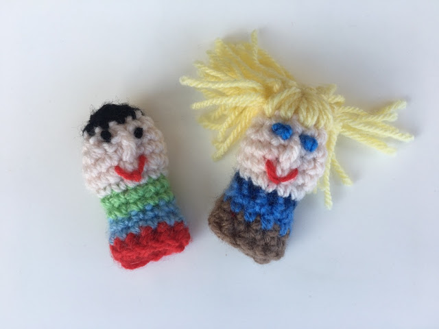 Two little finger puppets side by side on a white background. The left one has short black hair, a pale face with two black dotty eyes, a post stitch nose and a red embroidered mouth. The body is a striped crocheted cylinder striped from top to bottom: apple green, sky blue, red.  The right hand puppet has long yellow hair with satin stitch fringe, a pale face, blue oblong eyes, a post stitch nose and red embroidered mouth, The body is striped with a dark blue collar, then light blue and brown.